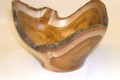 A laburnum natural edged bowl made from the crux of a tree (the junction where 2 branches come off the main stem).