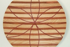 A laminated shallow plate made from 3 woods, the horizontal stripes are Ash and Myrtle and the petal shapes are Mahogany.