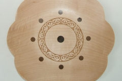 A shallow plate made from Maple with inserts of Walnut and a laser design in the centre.